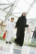 Woman and young boy walking in mall smiling (selective focus) - stock photo