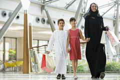 Woman and two young children walking in mall smiling (selective focus) Stock Photos
