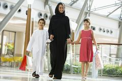 Woman and two young children walking in mall smiling (selective focus) - stock photo