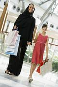 Woman and young girl walking in mall smiling (selective focus) - stock photo