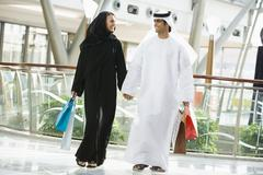 Couple walking in mall holding hands and smiling (selective focus) - stock photo