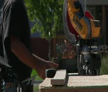 Man with sunglasses operates chop saw Stock Footage