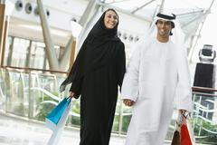 Couple walking in mall holding hands and smiling (selective focus) Stock Photos