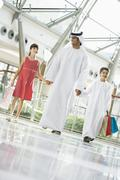 Man and two young children walking in mall holding hands and smiling (selective Stock Photos