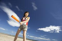 teenage girl playing baseball on beach - stock photo