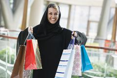 Woman standing in mall smiling (selective focus) - stock photo