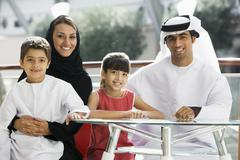 Family sitting indoors at table smiling (selective focus) Stock Photos