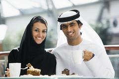 Couple at restaurant eating dessert and smiling (selective focus) Stock Photos