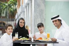 Family at restaurant eating and smiling (selective focus) Stock Photos