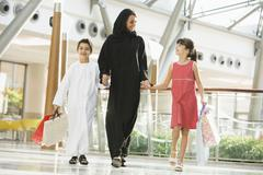 Woman and two young children walking in mall holding hands and smiling - stock photo