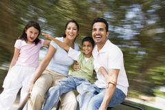Family outdoors in playground spinning and smiling (blur) - stock photo
