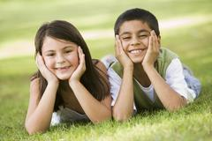 Two young children outdoors lying in park smiling (selective focus) - stock photo