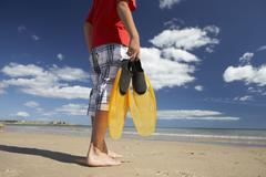 teenage boy on beach with flippers - stock photo