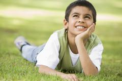 Young boy outdoors lying in grass and smiling (selective focus) - stock photo