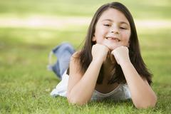 Young girl outdoors lying in grass and smiling (selective focus) - stock photo