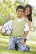 Two young children outdoors in park with ball smiling (selective focus) - stock photo