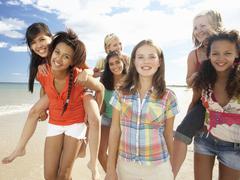 Teenage girls walking on beach Stock Photos