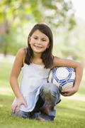Young girl outdoors at park holding ball and smiling (selective focus) - stock photo