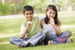 Two young children outdoors in park with ice cream smiling (selective focus) - stock photo