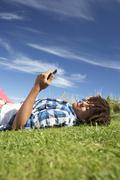 teenage boy lying on grass with phone - stock photo
