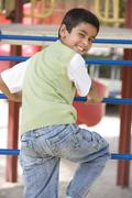 Young boy climbing on playground structure smiling (selective focus) - stock photo