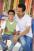 Father and son sitting on playground structure smiling (selective focus) - stock photo