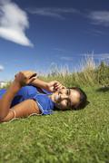 teenage girl lying on grass with mp3 player - stock photo