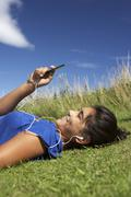 Teenage girl lying on grass with mp3 player Stock Photos