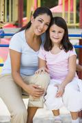 Mother and daughter girl sitting on playground structure smiling (selective - stock photo