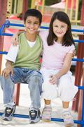 Two young children sitting on playground structure smiling (selective focus) - stock photo