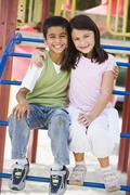 Stock Photo of Two young children sitting on playground structure smiling (selective focus)