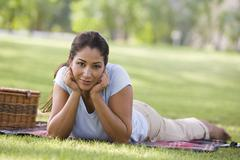 Woman lying outdoors at park with picnic basket smiling (selective focus) - stock photo