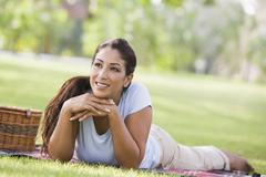Woman lying outdoors at park with picnic basket smiling (selective focus) Stock Photos