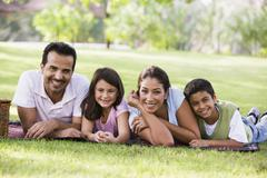 Family outdoors in park with picnic smiling (selective focus) - stock photo