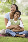 Mother and son outdoors in park bonding and smiling (selective focus) - stock photo