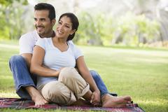 Couple sitting outdoors in park smiling (selective focus) - stock photo
