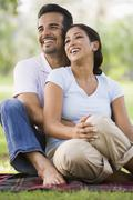Couple sitting outdoors in park smiling (selective focus) Stock Photos
