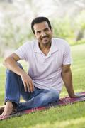 Man sitting outdoors at park smiling (selective focus) - stock photo