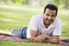 Man lying outdoors at park smiling (selective focus) Stock Photos
