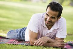 Stock Photo of Man lying outdoors at park smiling (selective focus)