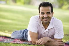 Man lying outdoors at park smiling (selective focus) - stock photo