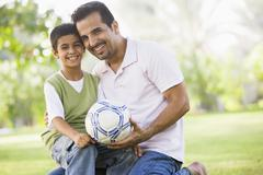 Father and son outdoors in park with ball smiling (selective focus) - stock photo