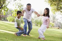 Two young children outdoors in park pulling smiling father by arms (selective Stock Photos