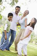Family outdoors in park bonding and smiling (selective focus) - stock photo
