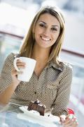 Woman at restaurant eating dessert and smiling (selective focus) Stock Photos