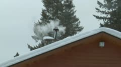 Smoky chimney on snowy roof Stock Footage