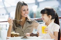 Mother at restaurant with daughter eating dessert and smiling (selective focus) Stock Photos