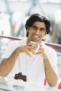 Man at restaurant eating dessert and smiling (selective focus) - stock photo