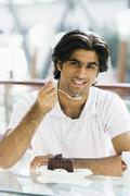 Man at restaurant eating dessert and smiling (selective focus) Stock Photos