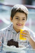 Young boy at restaurant eating dessert and smiling (selective focus) Stock Photos